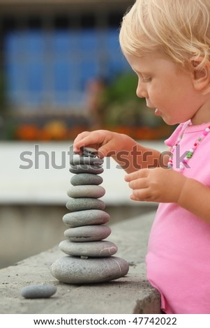 little girl wearing pink dress is building a construction from pebble stones. focus on fingers of right hand. - stock photo