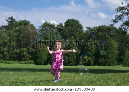 Little Girl Wearing Pink Outfit, Catching Bubbles in Grassy Park