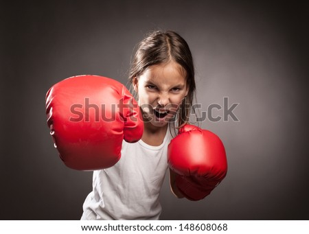 little girl wearing red boxing gloves - stock photo