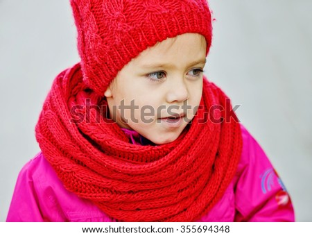 little girl wearing red scarf and hat in fall