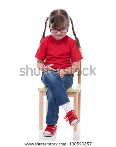 little girl wearing red t-shirt and glass posing on chair isolated on white