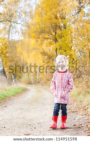 little girl wearing rubber boots in autumnal alley