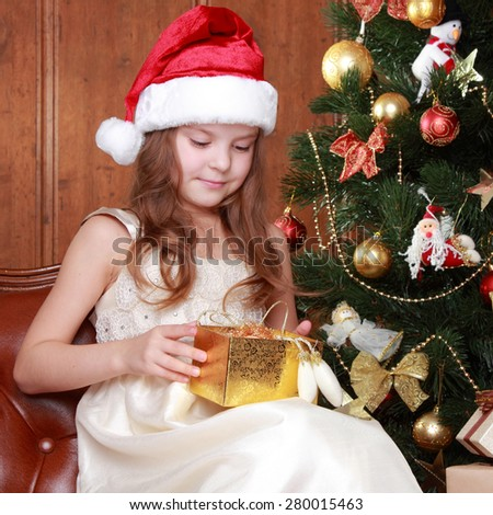 Little girl wearing santa claus red hat with christmas presents