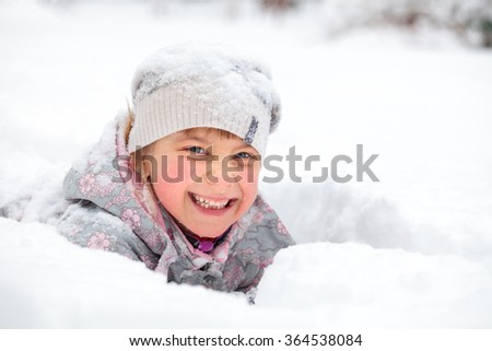 Little girl wearing winter clothing having fun laying in a fresh snow - stock photo