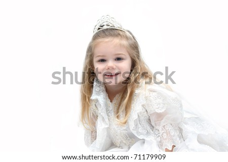 Little girl wears an elegant wedding dress and crown.  She is sitting in an all white room and smiling happily as she dreams of her getting married when she grows up.