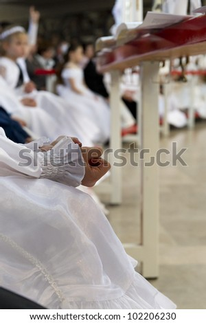 Little girl while clenching his hands during the communion - stock photo