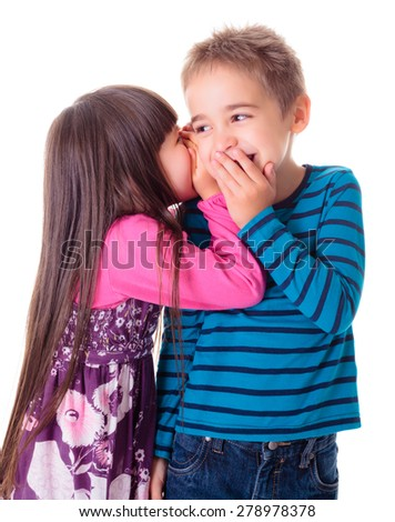 Little girl whispering interesting secret into boy's ear