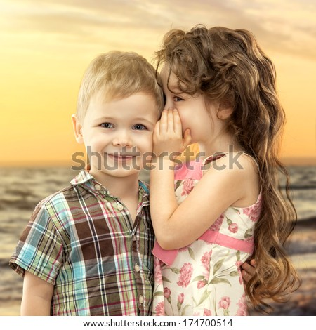 Little girl whispering something to boy on sea landscape at sunset. Love concept - stock photo