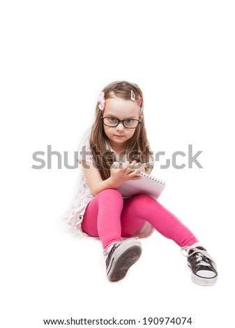 Little girl who writes on a notepad isolated on white background - stock photo