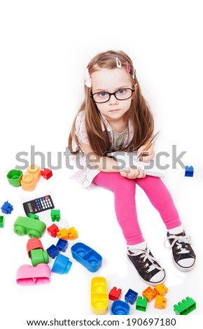Little girl who writes on a notepad surrounded by colorful toys - stock photo