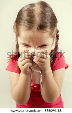 Little girl wipes her nose with a tissue.  - stock photo
