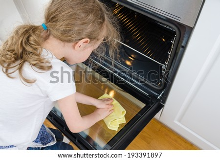 Little girl wipes oven in the kitchen at home.