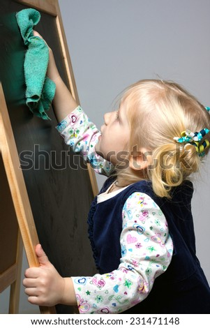 little girl wipes the board  - stock photo