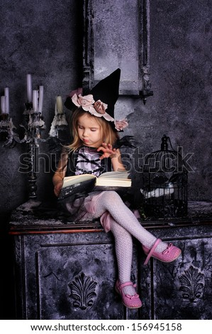 Little girl witch with a book in her hands and candles on halloween night - stock photo