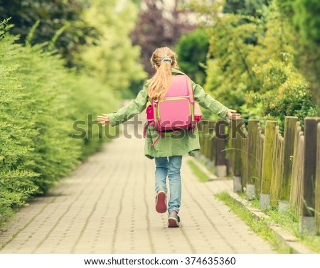 little girl with a backpack going to school. back view - stock photo