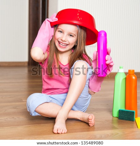little girl with a basin on her head sitting on the floor - stock photo