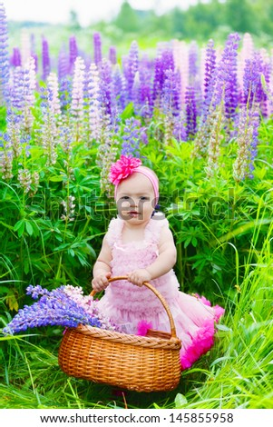 Little girl with a basket among blossoming lupines - stock photo