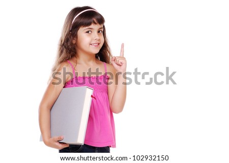 Little girl with a book pointing upwards at copy space against white background - stock photo