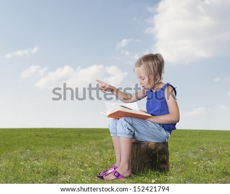 little girl with a book telling a story, outdoors  - stock photo
