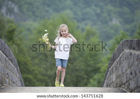 little girl with a bouquet of daisies walking on a bridge - stock photo