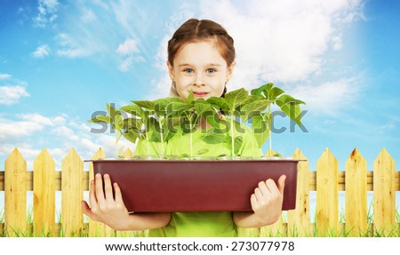 Little girl with a box of seedlings near the garden fence - stock photo