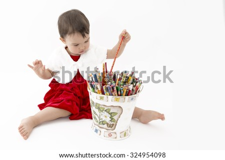 little girl with a bucket of colored pencils - stock photo
