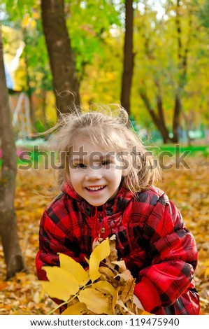 Little girl with a bunch of yellow leaves on a background of trees and foliage