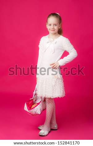 little girl with a cradle for a doll in the hands of - stock photo