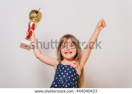 little girl with a cup. Girl winner. little girl won the competition. beautiful girl in a dress with a cup. the girl is happy.
