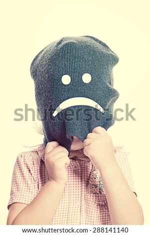Little girl with a face covered by a blue hat with an unhappy smiley, isolated - stock photo