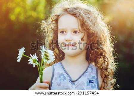 Little girl with a flower in her hand. Mothers day concept. Background toned in instagram filter. - stock photo