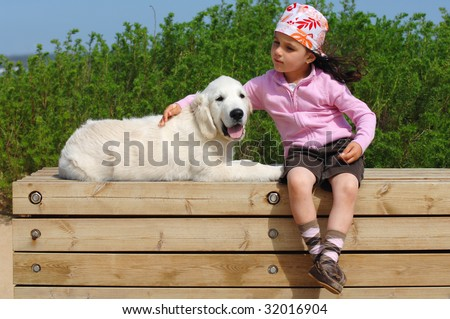 little girl with a Golden retriever puppy sitting near the beach