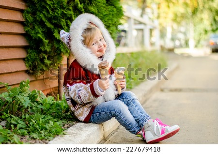 Little girl with a hood on her head eating ice cream while sitting on the sidewalk. Her mouth smeared with ice cream - stock photo