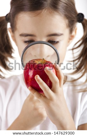 Little girl with a magnifying glass inspecting microbes on a red apple