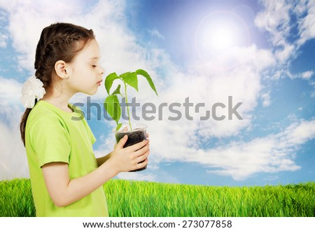 Little girl with a new green seedling outdoor in the field - stock photo