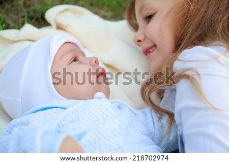 little girl with a newborn brother in the park