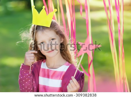 little girl with a paper crown  - stock photo