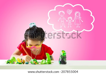Little girl with a pencil thinking about family and writing something on table.White cloud at the top of the photo - stock photo