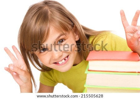 Little girl with a pile of books and showing victory sign, isolated over white - stock photo