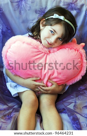 Little girl with a pink heart on violet background - stock photo