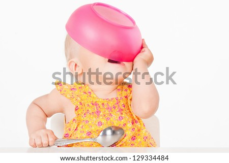 Little girl with a pink plate, on a gray background - stock photo