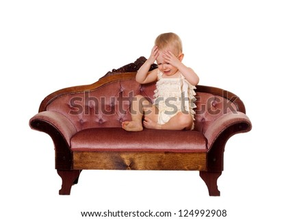 Little girl with a sad face having a time out on the couch. Isolated on a white background.