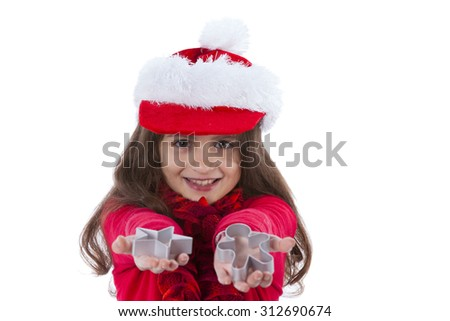 Little girl with a santa claus hat showing baking forms - stock photo