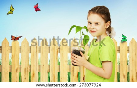 Little girl with a seedling in the pot in the garden - stock photo
