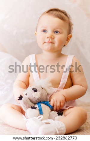 Little girl with a soft toy bear - stock photo