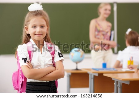Little girl with a teacher studying at school class - stock photo
