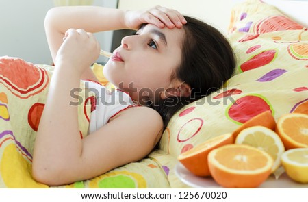 Little girl with a thermometer in bed - stock photo