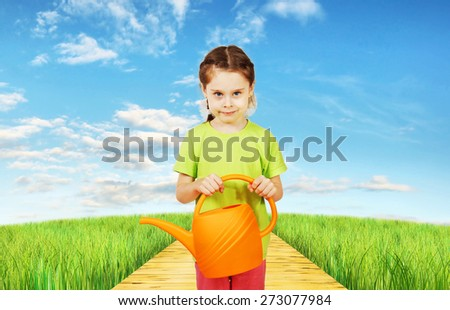 Little girl with a watering can stands in the field - stock photo