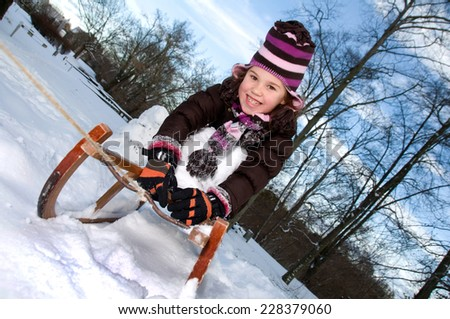 little girl with a wooden toboggan sled