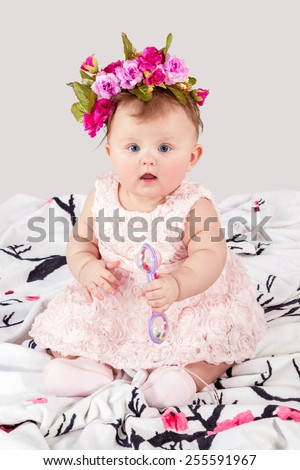 Little girl with a wreath of flowers on her head with a rattle in hands sitting on a blanket